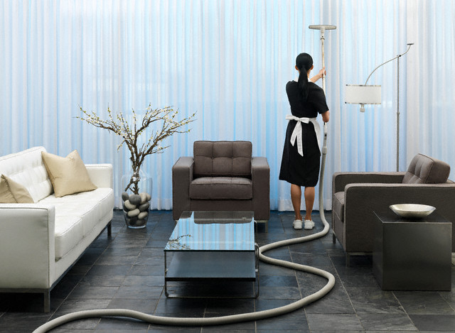 Maid vacuuming curtains --- Image by © Beau Lark/Corbis